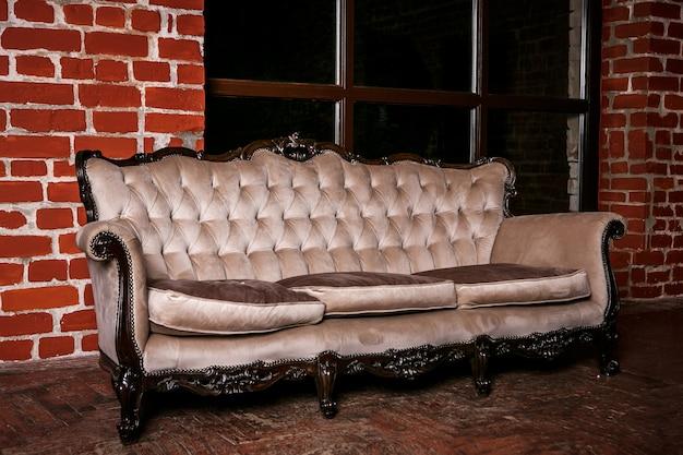 赤レンガの壁にベージュのソファ付きのリビングルーム Premium写真