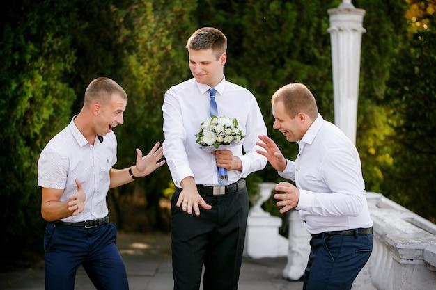 新郎は友人に結婚指輪を見せます Premium写真
