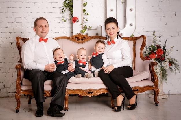大きな幸せな家族:母、父、三つ子の息子 Premium写真
