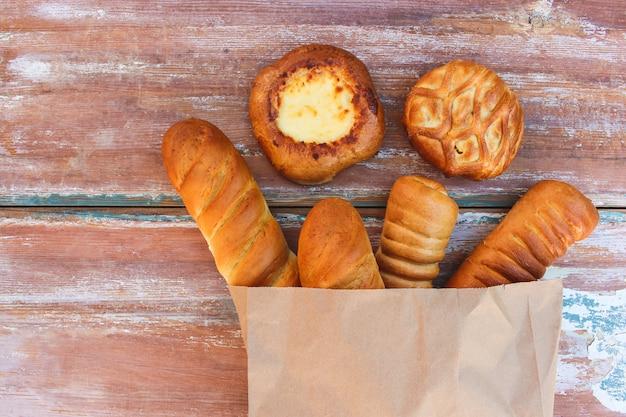 Хлебобулочные изделия в бумажном пакете на столе в виде сверху Premium Фотографии