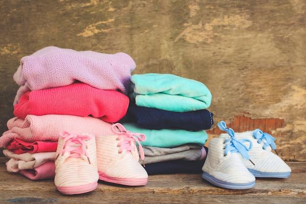ベビーシューズ、衣料品、おしゃぶり、古い木製の背景にピンクとブルー。トーンのイメージ Premium写真