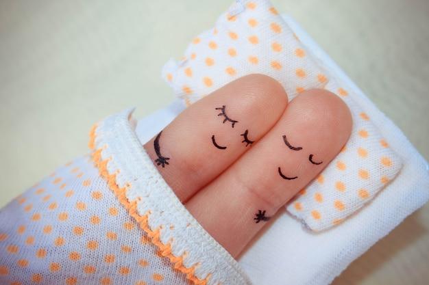 幸せなカップルの指アート。カップルはベッドで眠っています。 Premium写真