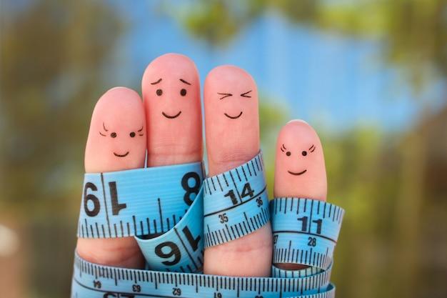 巻尺と幸せな家族の指アート。一緒に体重を減らすの概念。 Premium写真