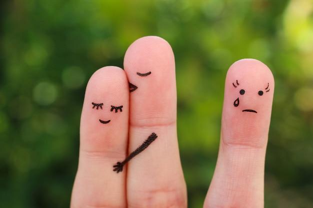 幸せなカップルの指アート。男は女を頬にキスします。女の子は嫉妬と怒りです。 Premium写真