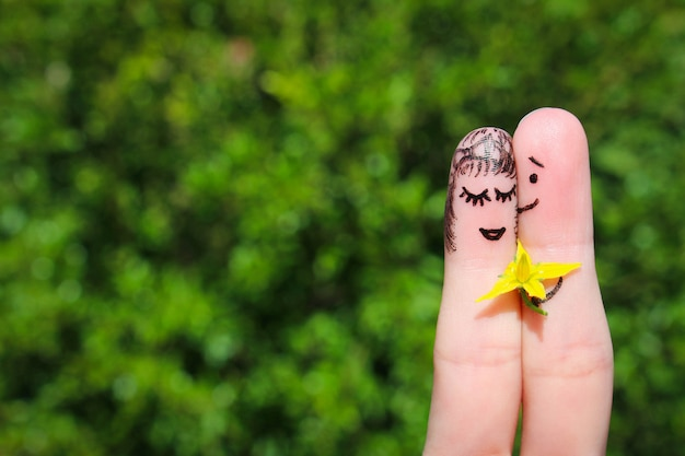 Лицо нарисовано на пальцах. мужчина дарит цветы женщине. Premium Фотографии