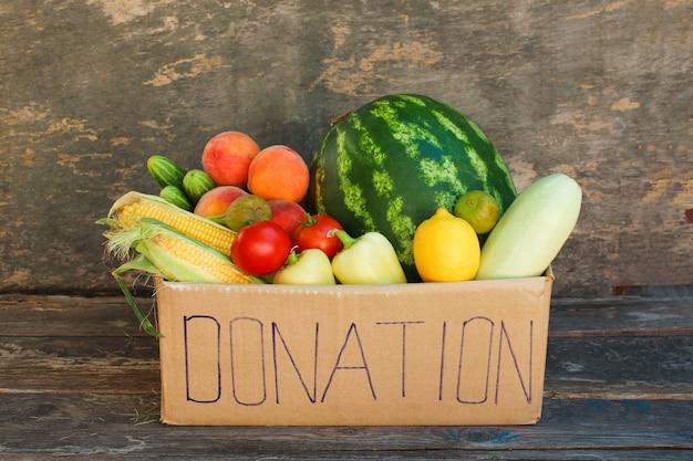 野菜や果物の古い木製の背景上の募金箱。 Premium写真