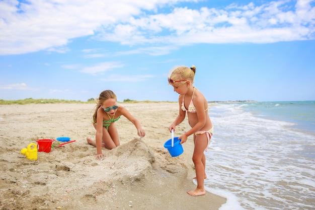 子供たちはビーチで砂と遊ぶ。 Premium写真