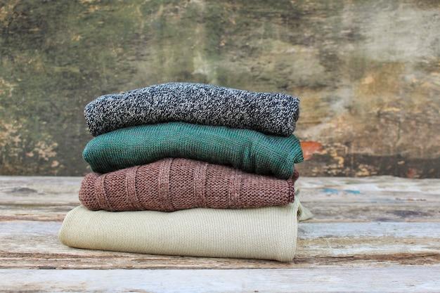 木製の背景にカラフルな暖かい服の山。トーンのイメージ Premium写真