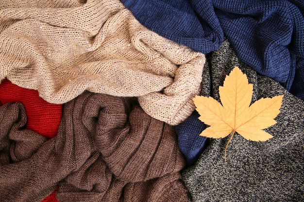 木製の背景にカラフルな暖かい服の山 Premium写真