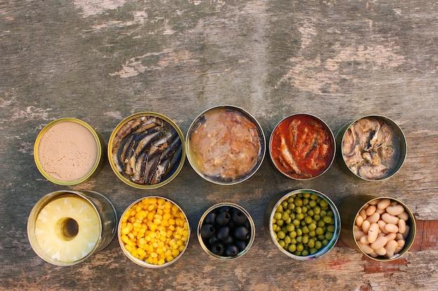 古い木製の背景に異なるオープン缶詰 Premium写真