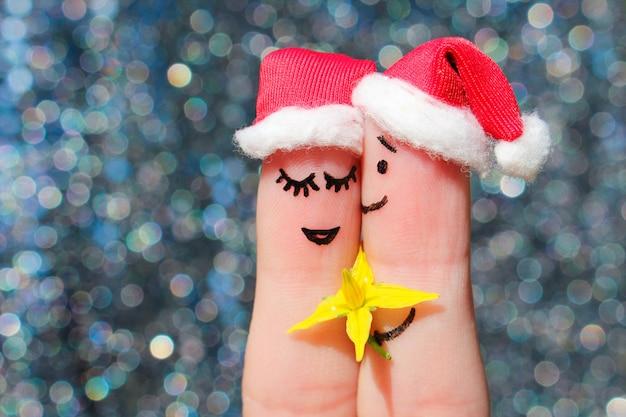幸せなカップルの指アートはクリスマスを祝います。男性は女性に花をあげています。 Premium写真