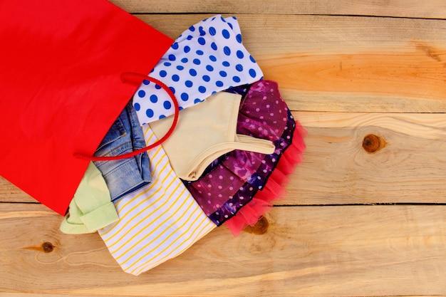 女性の服は、木製の背景に紙の買い物袋から落ちる。 Premium写真