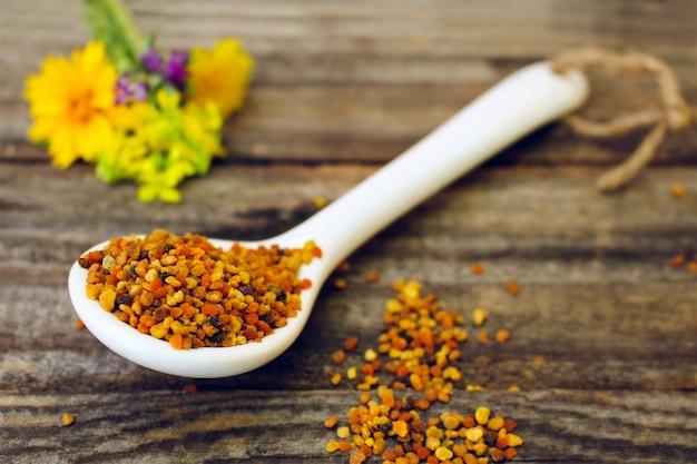 古い木製の背景に蜂の花粉と野の花。トーンのイメージ Premium写真