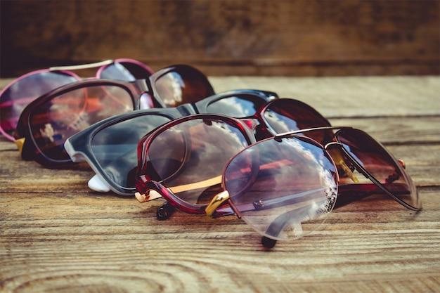 木製の背景にさまざまなサングラス。雲と木のサングラスの反射。 Premium写真