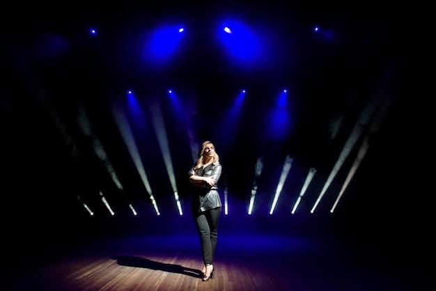 Красотка артиста на фоне размытых прожекторов на сцене Premium Фотографии
