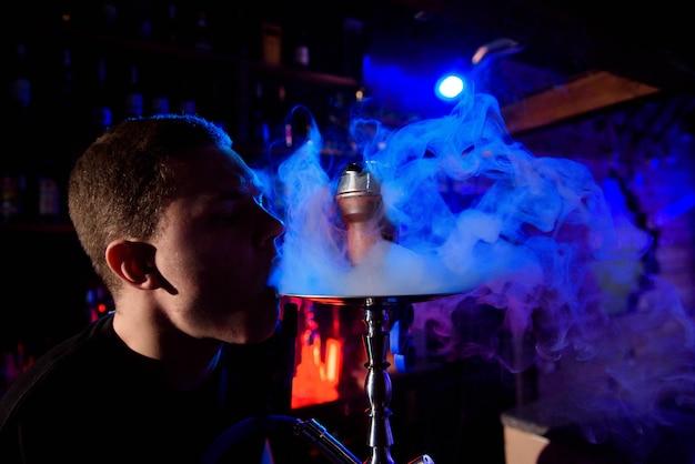 伝統的な水ギセルパイプを喫煙し、水ギセルカフェで煙を吐き出す男。 Premium写真