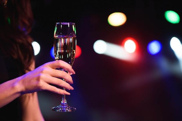 Красивая молодая женщина пьет шампанское на вечеринке над огнями Premium Фотографии