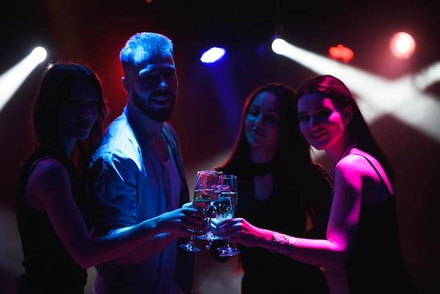 手でシャンパンのグラスと踊る若い友人。 Premium写真