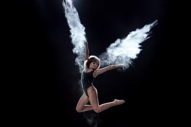 シーンの黒い背景に小麦粉と踊っている女の子 Premium写真