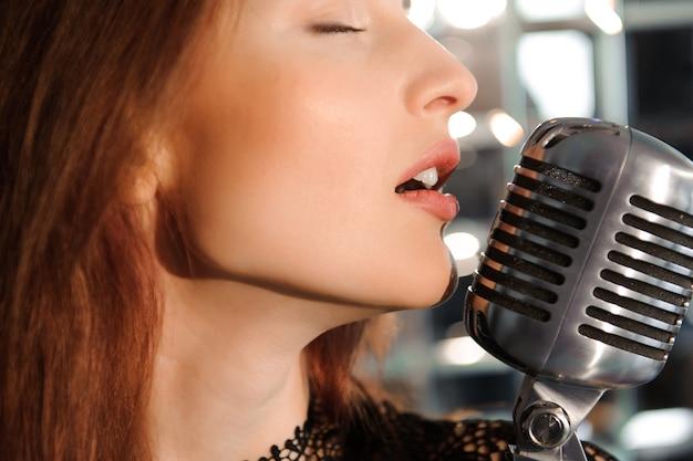 ロックスター。レトロなマイクで歌っているセクシーな女の子。 Premium写真