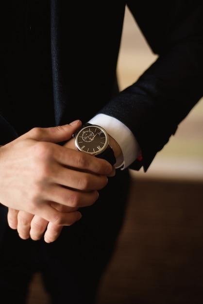 男性ビジネスマンは、会議の準備をする彼の時計を服を着て調整します。時計 Premium写真