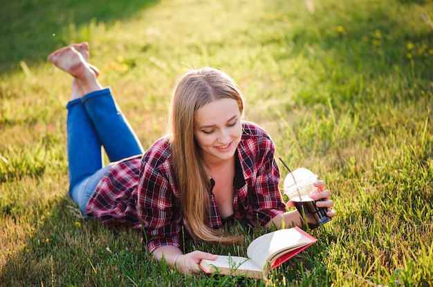 夏の公園で本を読んでいる女の子 Premium写真