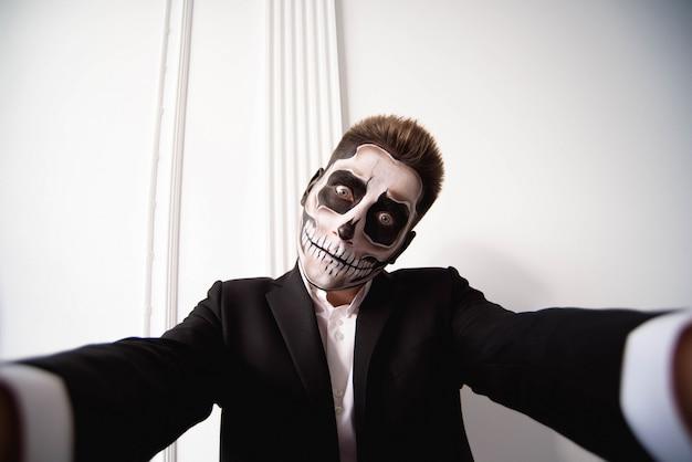 頭蓋骨は、ハロウィーンの顔アート、若い男の肖像画を作る Premium写真