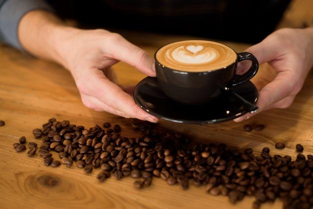 Портрет профессионального бариста в фартуке с чашкой горячего кофе в кафе Premium Фотографии