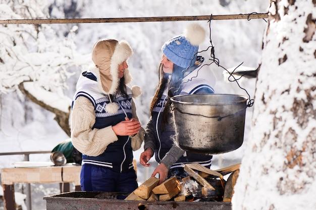 Две подружки, приготовление пищи в природе на пожаре в котле. девушки греются у костра зимой. Premium Фотографии