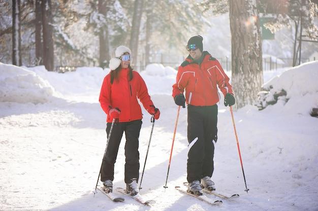 スキー、雪、冬の楽しみ、幸せな家族は森でスキーをしています。 Premium写真