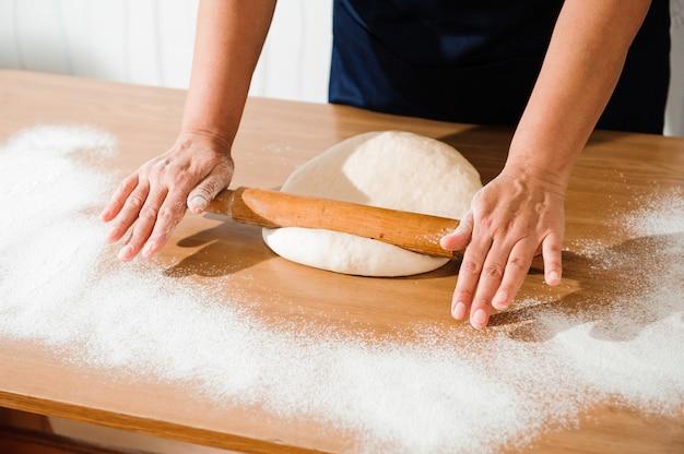 生地を練り、生地に白い小麦粉を振りかけます。 Premium写真