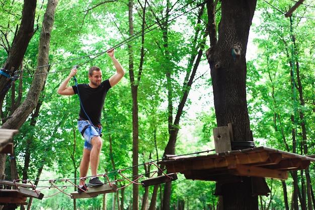 安全なギアでロープ公園の若い男でハイキング。 Premium写真