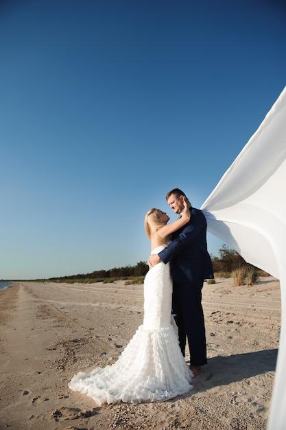 Жених и невеста у моря в день свадьбы Premium Фотографии