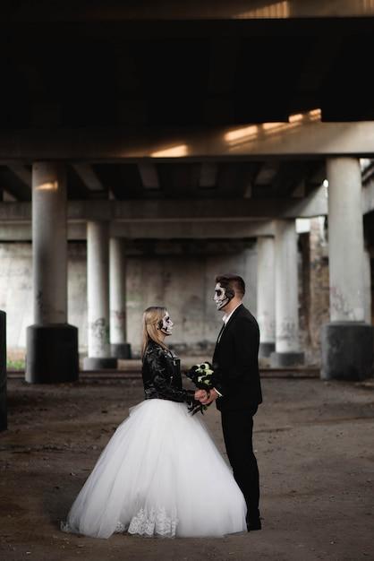 Хэллоуин пара одетый в свадебную одежду романтический зомби Premium Фотографии