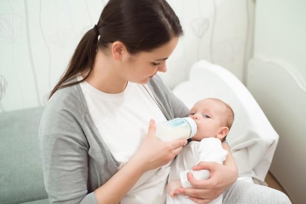 幸せな笑顔の母親と赤ちゃんが自宅のベッドで刺して、赤ちゃんは牛乳を食べます。 Premium写真
