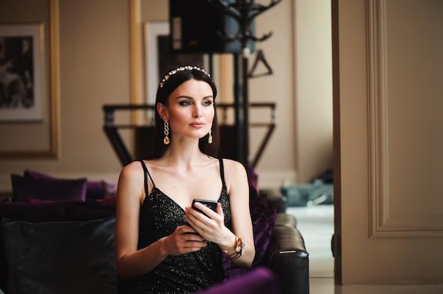 携帯電話でホテルの美しいブルネット。 Premium写真