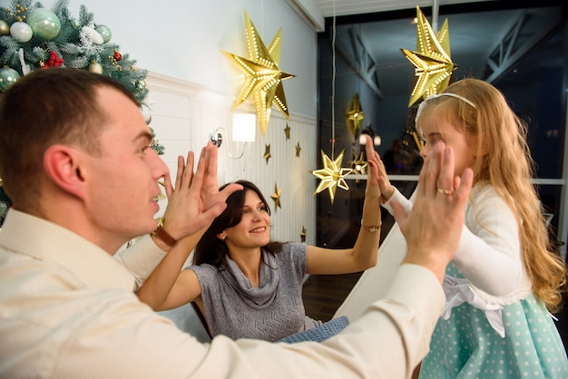 クリスマスの背景に近い幸せな笑顔の家族がお互いに遊びます。 Premium写真