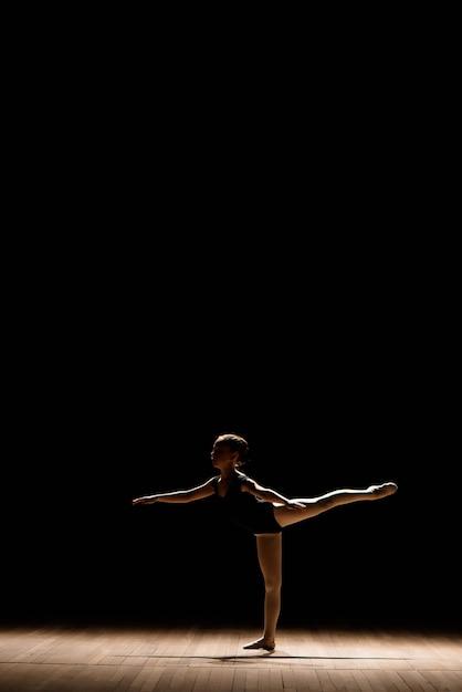 ステージ上で踊るダークバレエ衣装でかわいい小さなバレリーナ。ダンスクラスで子供します。子供の女の子はバレエを勉強しています。 Premium写真