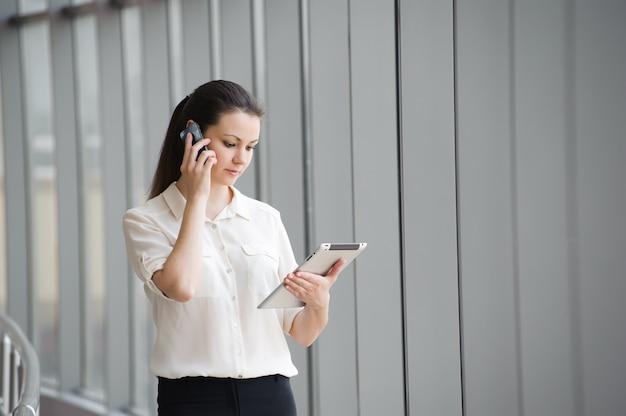 Молодая коммерсантка говоря на мобильном телефоне пока готовящ окно в офисе. красивая молодая женская модель в офисе. Premium Фотографии