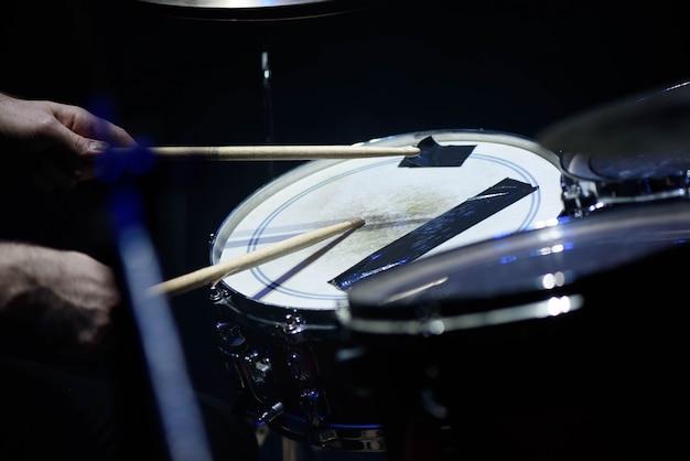 Мужчина играет на музыкальном ударном инструменте с палочками крупным планом Premium Фотографии