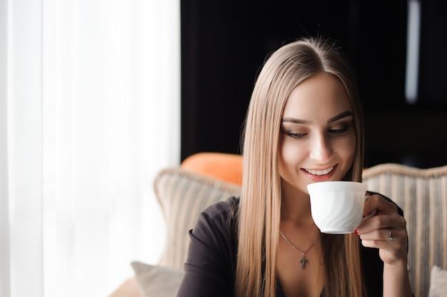 カフェでコーヒーを飲みながら携帯電話を使用して若い女性 Premium写真
