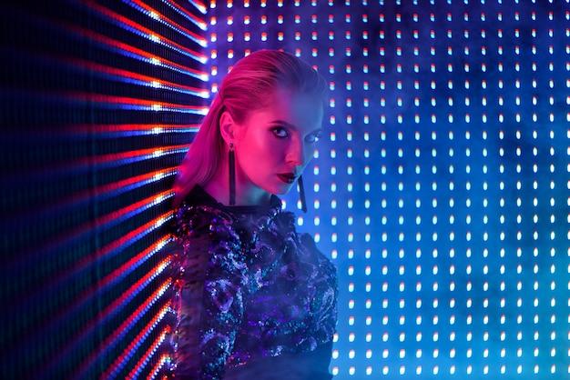 ナイトクラブでネオンの光でディスコダンサー。ネオンの光のファッションモデルの女性 Premium写真