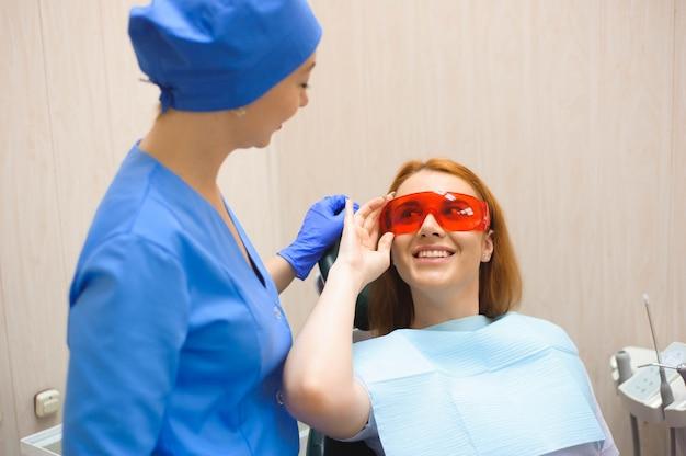 Молодая женщина, имеющая медицинский осмотр в офисе стоматолога у врача Premium Фотографии