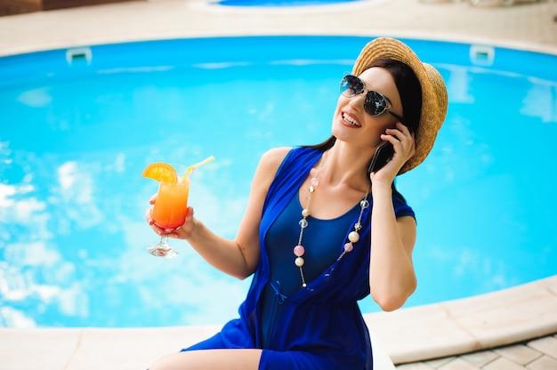 スイミングプールのそばの電話と美しい若い女性 Premium写真