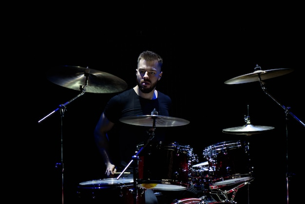 Музыка, люди, музыкальные инструменты и концепция развлечений - мужской музыкант с барабанными палочками играет на барабанах и тарелках на концерте или в студии Premium Фотографии
