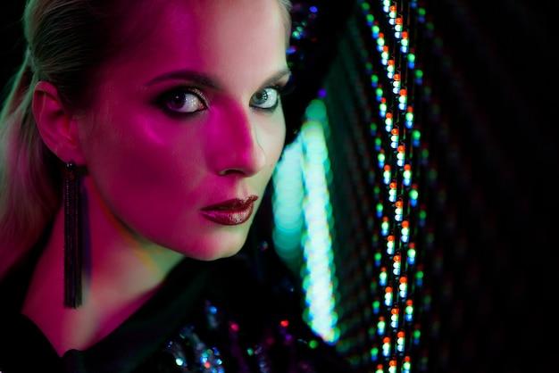 セクシーな女の子のファッション写真は、ナイトクラブで黒に身を包んだ。ナイトクラブの女の子ネオンのコンセプトです。 Premium写真