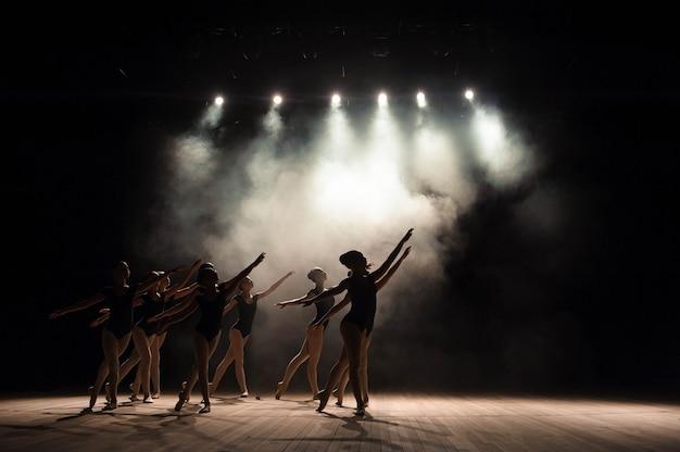 光と煙のある劇場の舞台でのバレエのクラス。子供たちはステージで古典的な運動に従事しています。 Premium写真