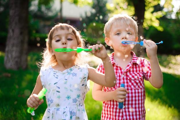 Малыш и друзья играют в пузырь на детской площадке с закатом Premium Фотографии