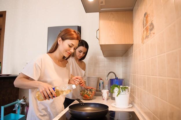 友人は朝食を準備し、一緒にキッチンで食事をします。 Premium写真