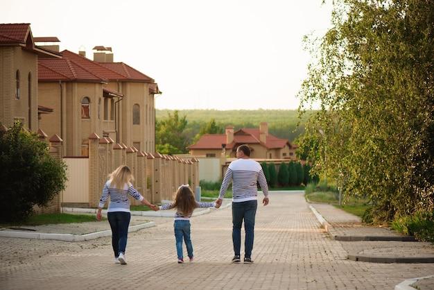 夏の時間を歩いて楽しんでいる少女と幸せな妊娠中の家族。 Premium写真